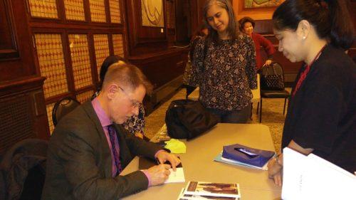 Tomlinson signs a copy of his book for ConGen Tess de Vega.